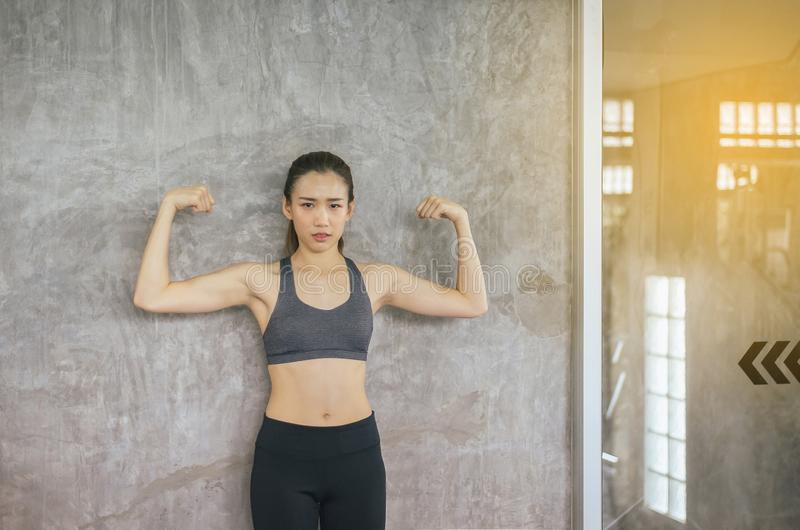 Strong asian woman posture standing and lifting up her arms and exercises muscle at gym royalty free stock photo