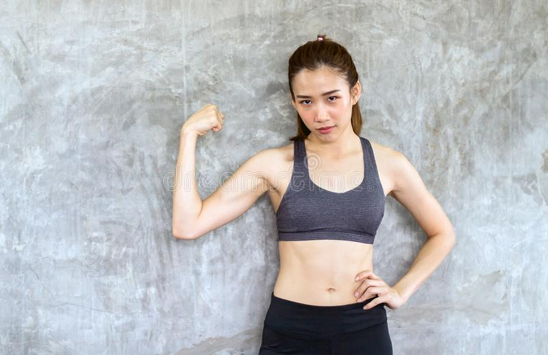 Strong asian female posture standing and lifting up her arms and exercises muscle at gym royalty free stock photo