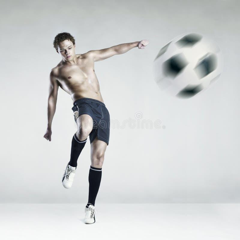 Strong athlete kicking the ball stock photos