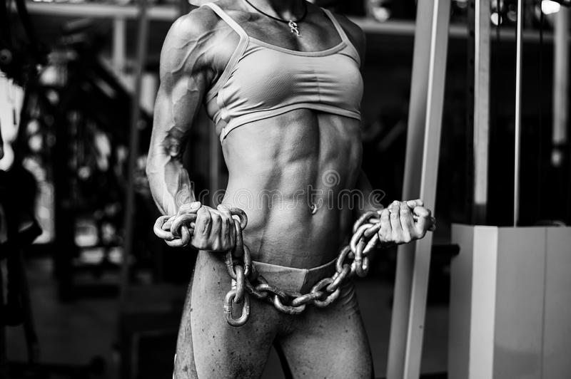 Strong athletic female body. Muscular woman with heavy chain stock photo