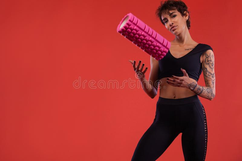 Fitness and sport motivation.. Strong and fit athletic, woman with tattoo posing on red background in sportswear. A Strong athletic, female runner on the black royalty free stock image
