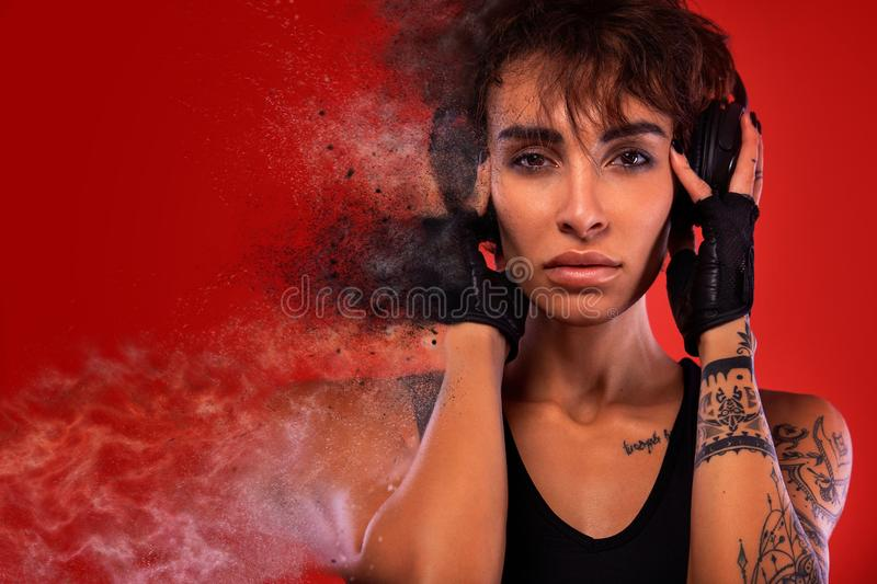 Fitness and sport motivation.. Strong and fit athletic, woman with tattoo posing on red background in sportswear. A Strong athletic, female runner on the black stock photography