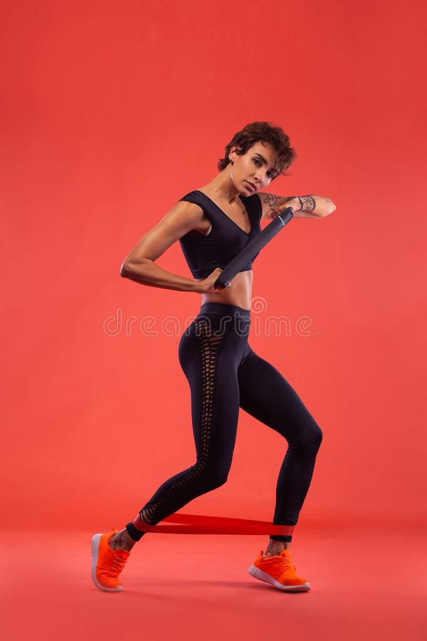 Fitness and sport motivation.. Strong and fit athletic, woman with tattoo posing on red background in sportswear. A Strong athletic, female runner on the black stock image