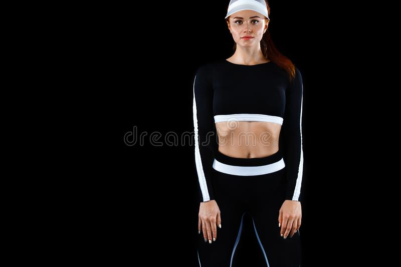 Strong athletic woman , posing on black background wearing in sportswear. Energy fitness and sport motivation. Copy. A Strong athletic, female runner on the stock images