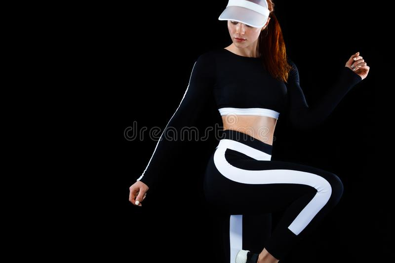 Strong athletic woman , posing on black background wearing in sportswear. Energy fitness and sport motivation. Copy. A Strong athletic, female runner on the stock photo