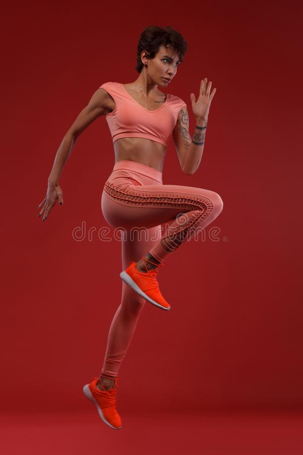 A strong athletic, woman sprinter or runner, running on red background wearing sportswear. Fitness and sport motivation. A Strong athletic, female runner on the royalty free stock photo