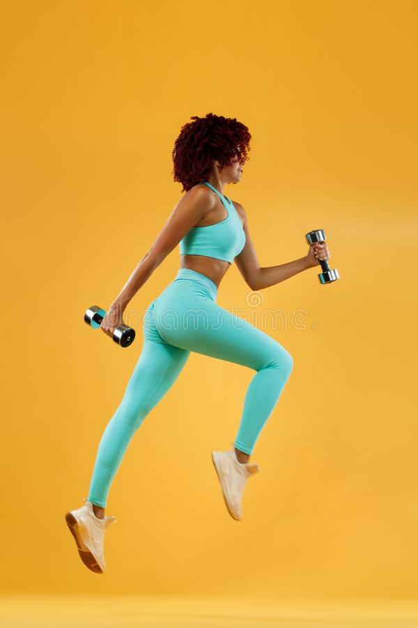 Strong athletic, woman sprinter or runner, running on yellow background with dumbbells wearing sportswear. Fitness and sport motiv. A Strong athletic, female royalty free stock photography