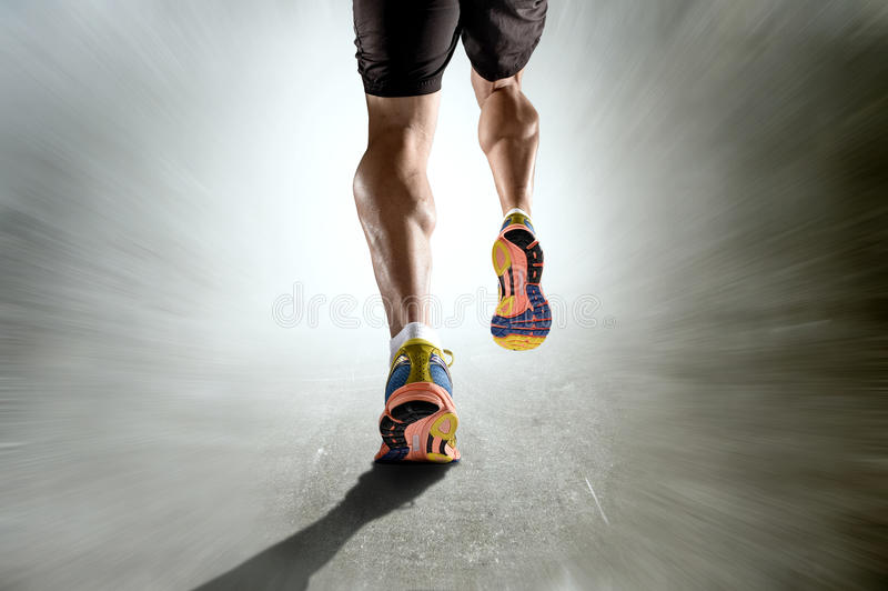 Strong athletic legs with ripped calf muscle of sport man running on motion grunge background. Close up view strong athletic legs with ripped calf muscle of royalty free stock photo