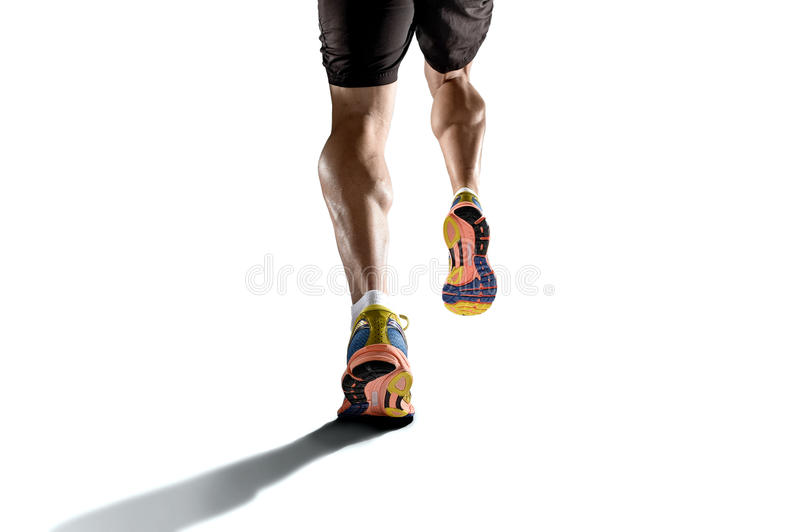 Strong athletic legs with ripped calf muscle of young sport man running isolated on white background. Close up view strong athletic legs with ripped calf muscle royalty free stock image