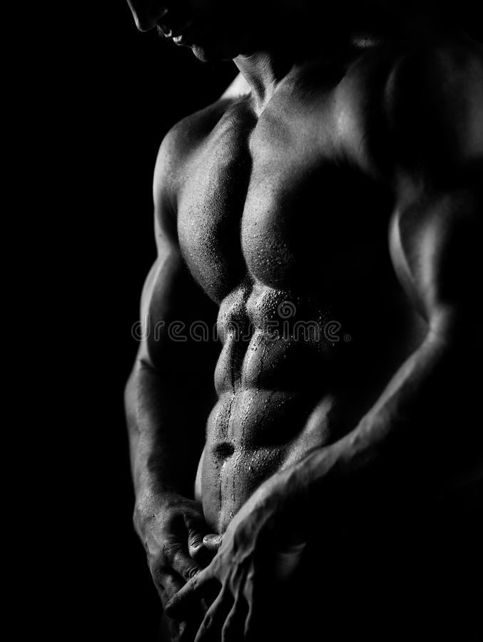 Strong athletic man on dark background royalty free stock photography