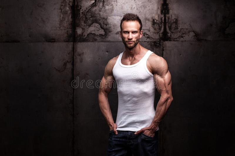 Strong athletic man on dark grunge background. Studio shot of strong athletic man wearing white shirt on dark grunge background royalty free stock photography