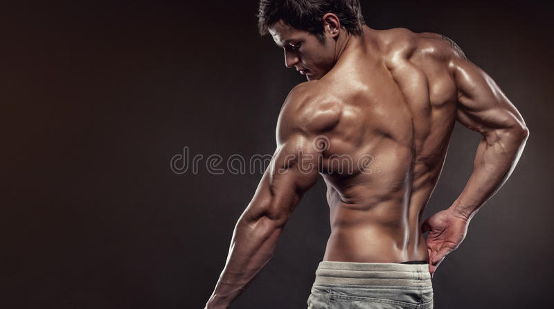 Strong Athletic Man Fitness Model posing back muscles with trice stock images