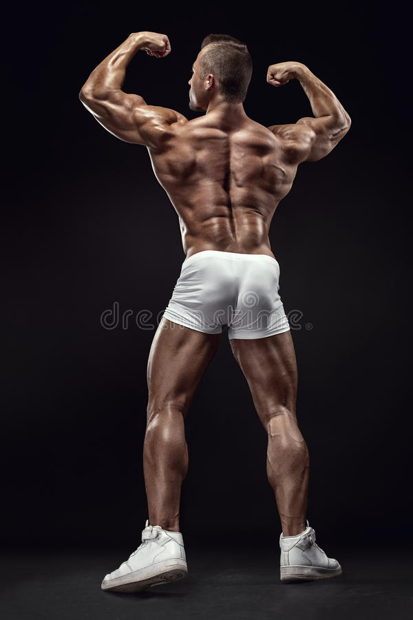 Strong Athletic Man Fitness Model posing back muscles, triceps,. Latissimus over black background stock photography