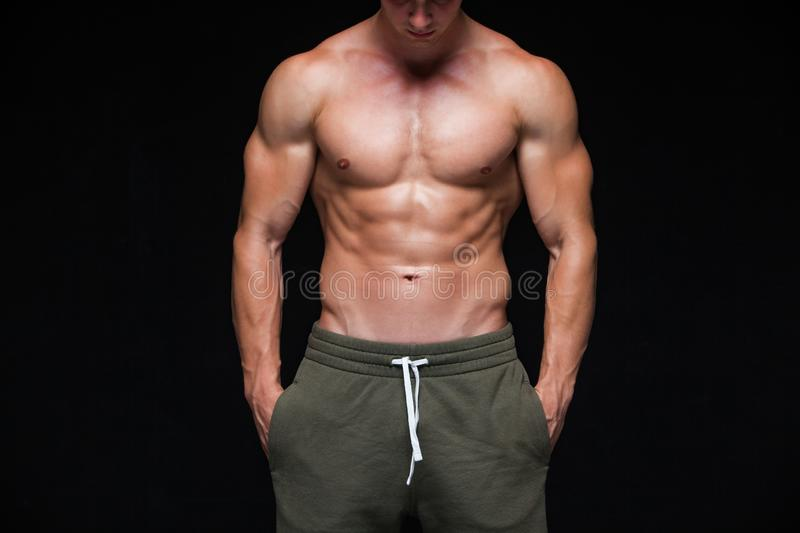 Strong Athletic Man - Fitness Model showing his perfect body isolated on black background with copyspace. Bodybuilder. Man with perfect abs, shoulders,biceps royalty free stock photo