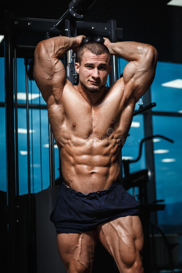 Strong Athletic Man Fitness Model Torso showing muscles in gym royalty free stock image