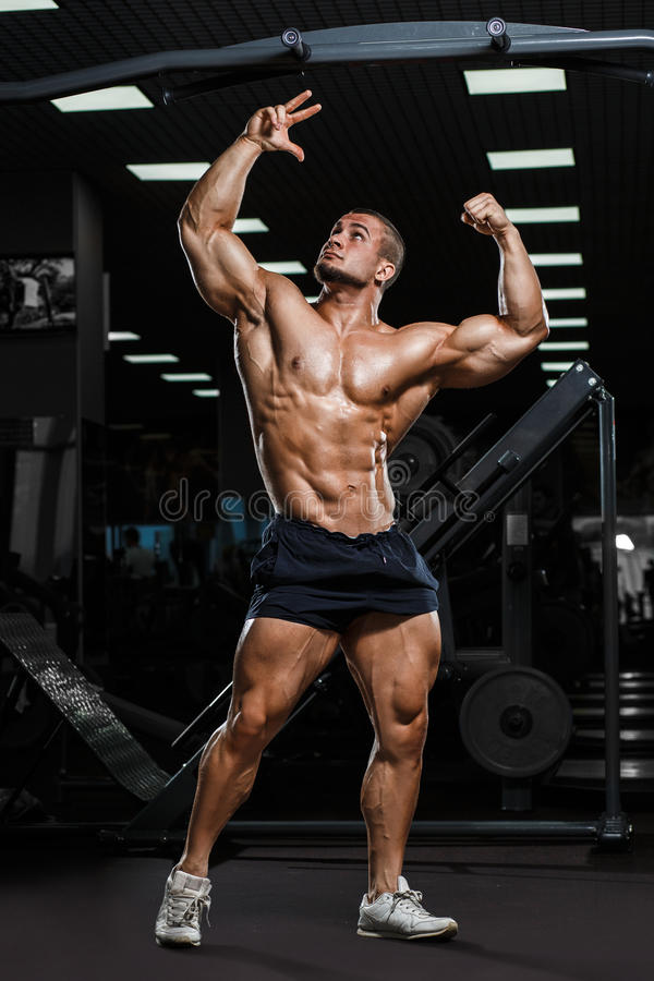 Strong Athletic Man Fitness Model Torso showing muscles in gym. Strong Athletic Man Fitness Model Torso showing abs torso muscles in gym stock photos