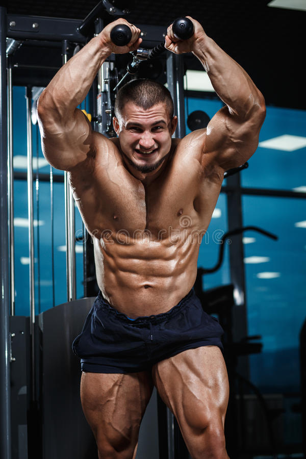 Strong Athletic Man Fitness Model Torso showing muscles in gym. Strong Emotional Athletic Man Fitness Model Torso showing abs torso muscles in gym royalty free stock image
