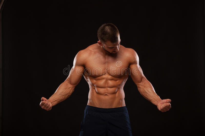 Strong Athletic Man Fitness Model Torso showing six pack abs. isolated on black background with copyspace is looking at royalty free stock photography