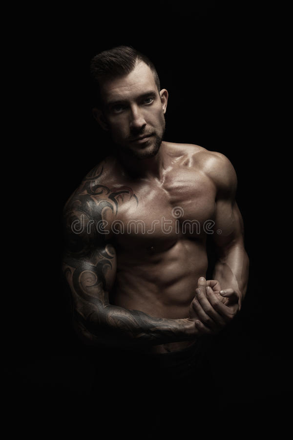 Strong athletic man showes naked muscular body. Strong athletic man. Handsome male fitness model showing naked torso, muscular body. Strong muscles and biceps royalty free stock photo