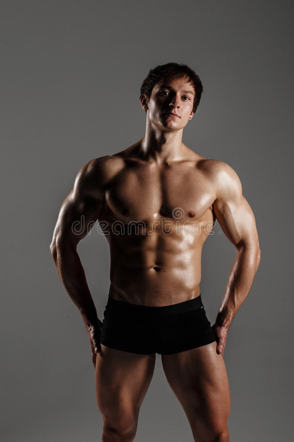 Strong Athletic Man showing muscular body and sixpack abs. Showing his body. FITNESS MODEL. Great for Underwear Commercial. Wet b royalty free stock photo