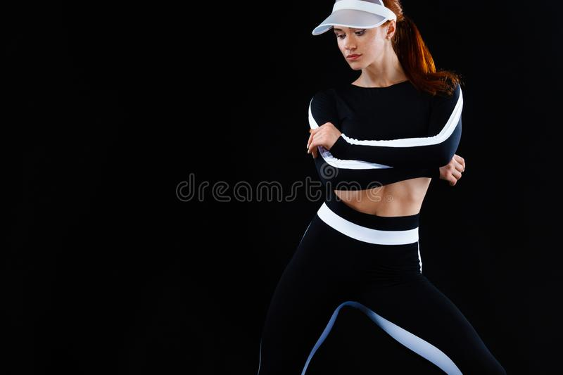 Strong athletic woman , posing on black background wearing in sportswear. Energy fitness and sport motivation. Copy. A Strong athletic, female runner on the stock photos