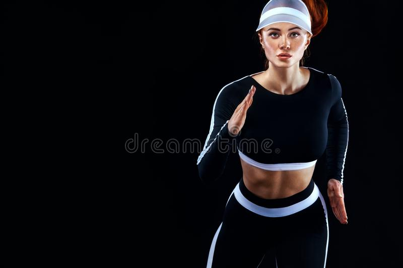 Strong athletic woman sprinter, running on black background wearing in the sportswear. Fitness and sport motivation. A Strong athletic, female runner on the royalty free stock image