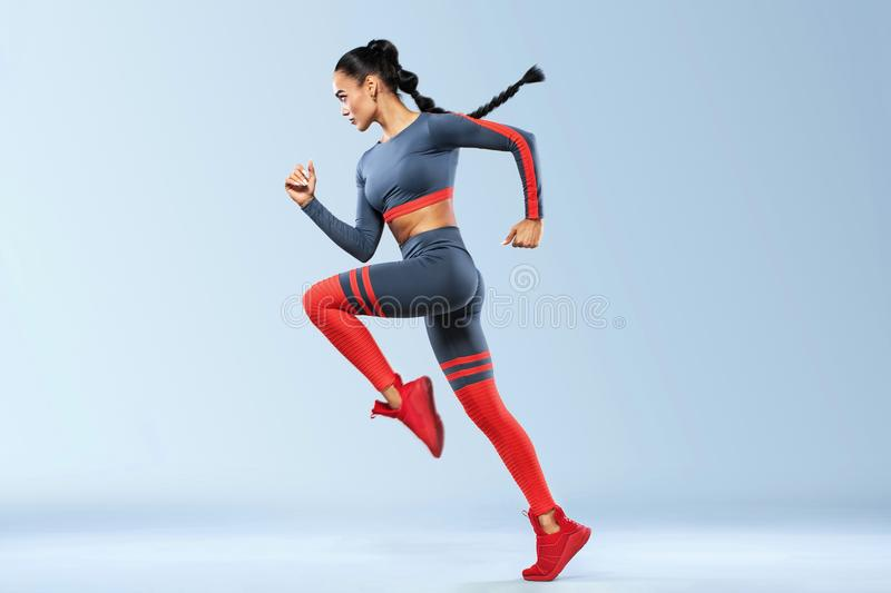 A strong athletic, women sprinter, running wearing in the sportswear, fitness and sport motivation. Runner concept with stock photo
