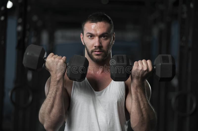 Strong Athletic Young Man With Dumbbells. In Hands. Sporty Athlete Posing on Background of Gym stock images