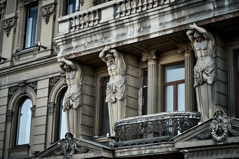 Strong Atlants is supporting balcony on the facade of historical building in Saint-Petersburg royalty free stock photos