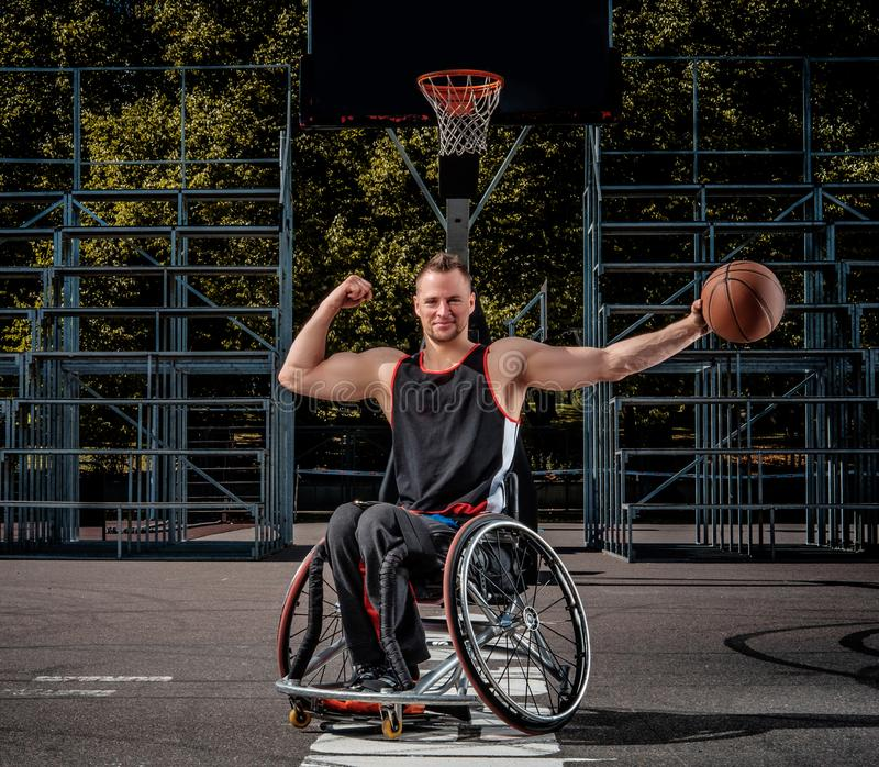 Smiling cripple basketball player in wheelchair holds a ball on open gaming ground. Strong basketball player in a wheelchair pose with a ball on open gaming stock photos