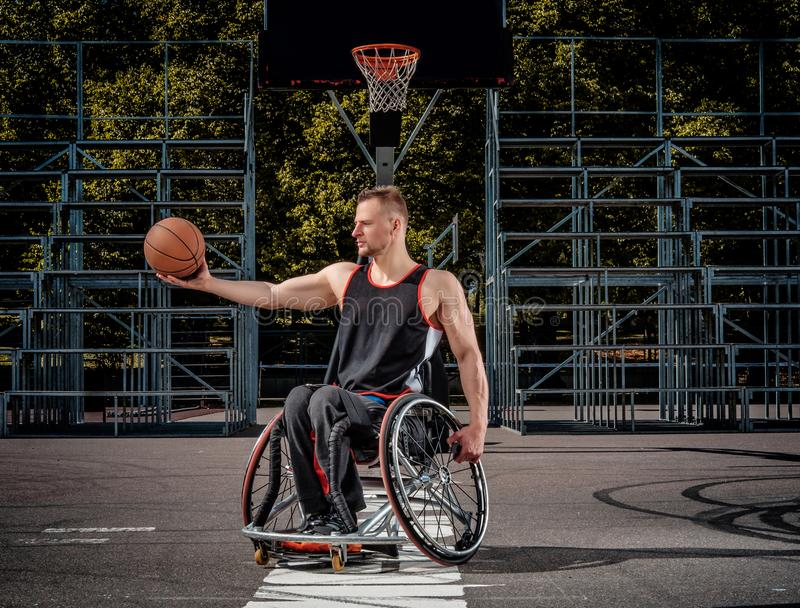 Smiling cripple basketball player in wheelchair holds a ball on open gaming ground. Strong basketball player in a wheelchair pose with a ball on open gaming stock photo