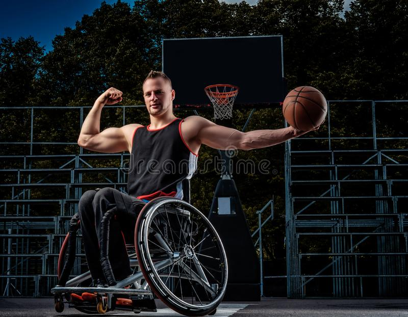 Strong basketball player in wheelchair pose with a ball on open gaming ground. Strong basketball player in a wheelchair pose with a ball on open gaming ground royalty free stock photography