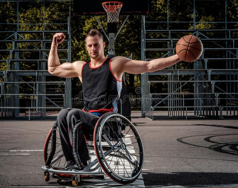 Strong basketball player in wheelchair pose with a ball on open gaming ground. Strong basketball player in a wheelchair pose with a ball on open gaming ground stock image