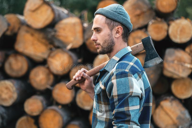 Strong bearded lumberjack holds ax on his shoulder stock photography