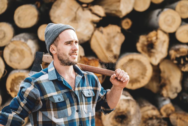 Strong bearded lumberjack wearing plaid shirt hold ax in hand on background of sawmill royalty free stock photo