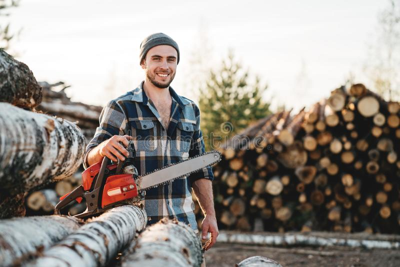 Strong bearded lumberjack wearing plaid shirt hold chainsaw in hand on background of sawmill royalty free stock photos
