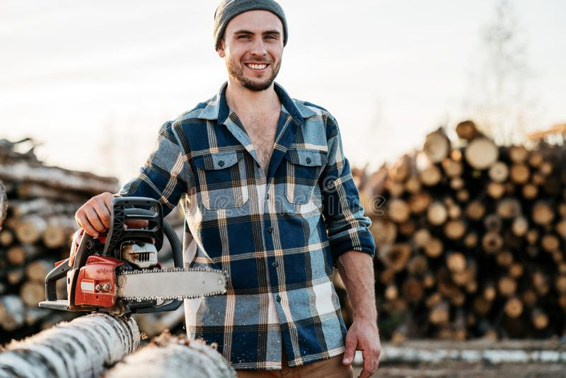 Strong bearded lumberjack wearing plaid shirt hold chainsaw in hand on background of sawmill stock photo