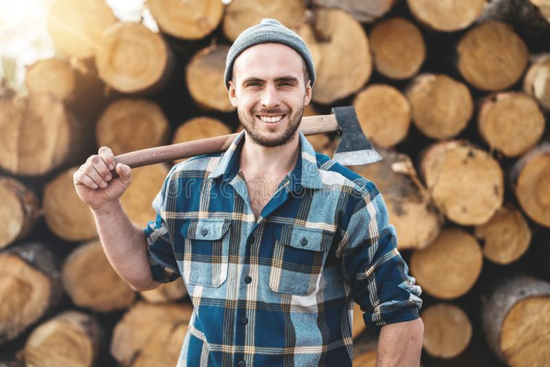 Strong bearded lumberjack wearing plaid shirt holds ax on his shoulder royalty free stock photo