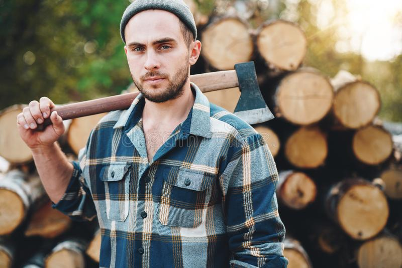 Strong bearded lumberman holds ax on his shoulder on warehouse of logs royalty free stock photography