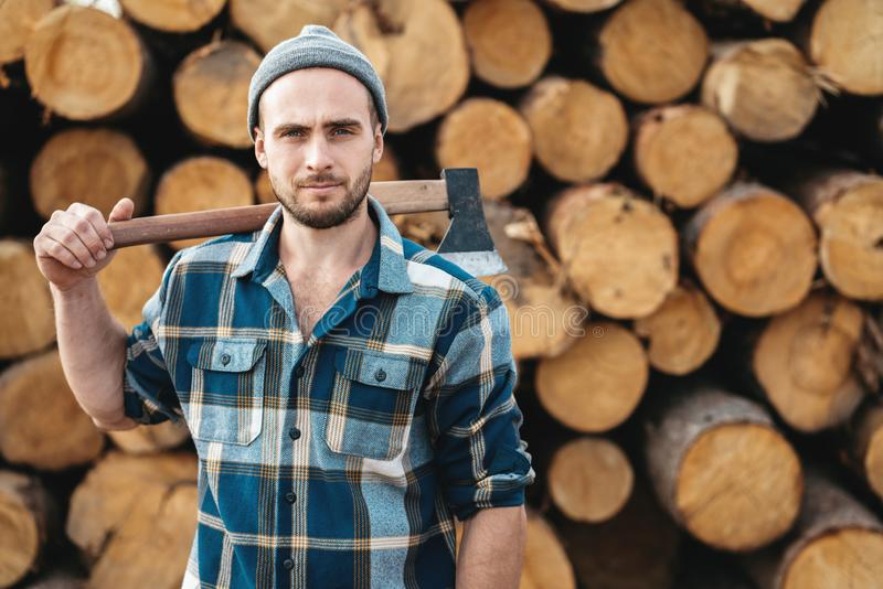 Strong bearded lumberman wearing plaid shirt holds axe on his shoulder royalty free stock image