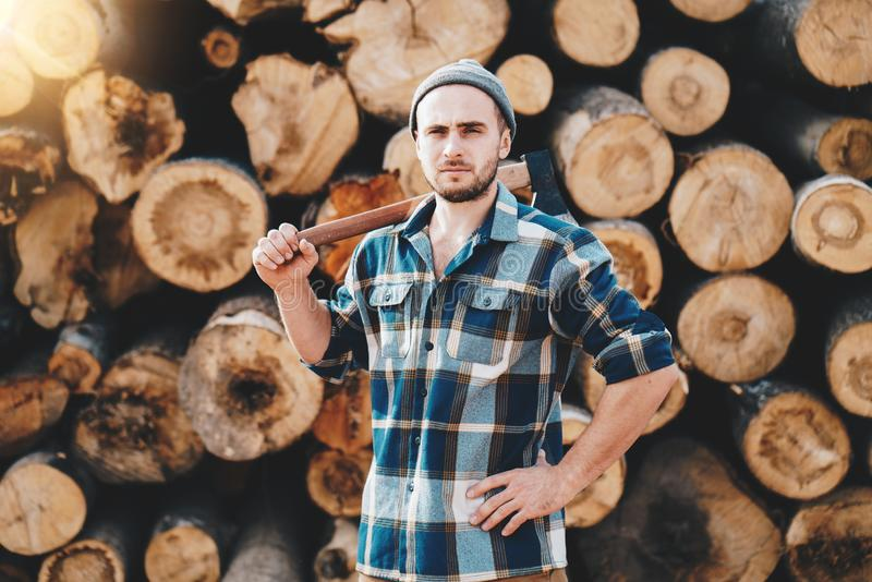Strong bearded lumberman wearing plaid shirt holds axe on his shoulder stock photos