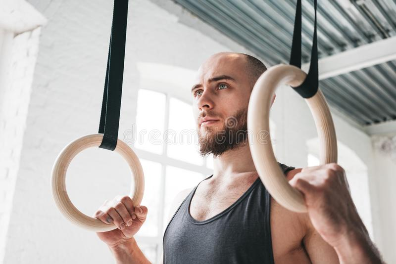 Strong bearded man holding gymnastic rings at gym stock photo