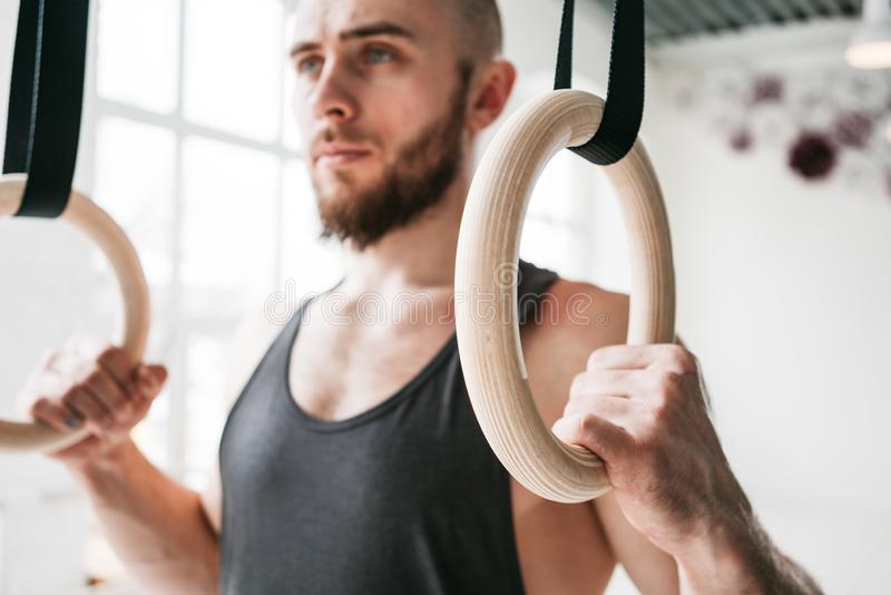 Strong bearded man holding gymnastic rings at gym royalty free stock photo