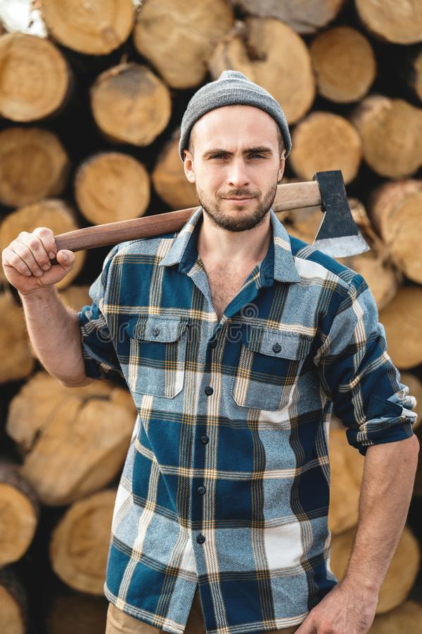 Strong bearded woodcutter holds axe on his shoulder on warehouse of logs stock image