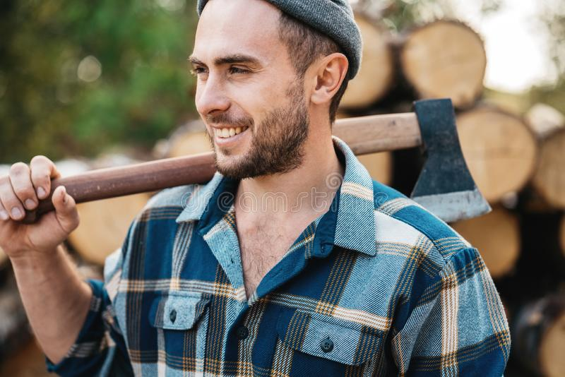 Strong bearded woodcutter holds axe on his shoulder on warehouse of logs royalty free stock photo