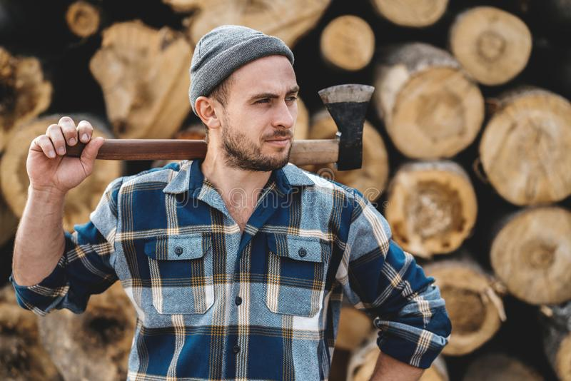 Strong bearded woodcutter wearing plaid shirt hold axe in hand on background of sawmill stock photos