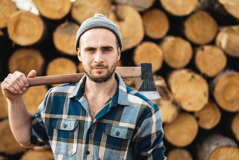 Strong bearded woodcutter wearing plaid shirt hold axe in hand on background of sawmill royalty free stock photography