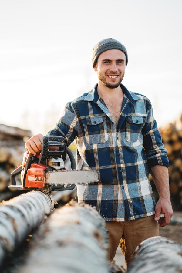 Strong bearded woodcutter wearing plaid shirt hold chainsaw in hand on background of sawmill and warehouse of trees royalty free stock photos