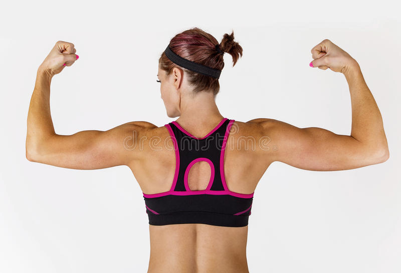 Strong Beautiful fitness woman flexing her arm and back muscles. Beautiful strong muscular woman flexing her biceps and arm muscles. View from behind to show her stock image