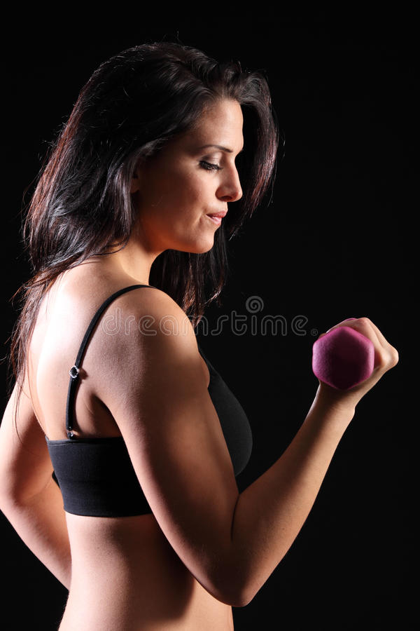 Strong beautiful girl bicep curl exercise in gym. Bicep curl by beautiful young caucasian girl working out with fitness hand weights, wearing black sports bra royalty free stock photos